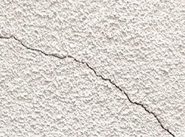 外壁にひびが入っている、白い粉が手に付く